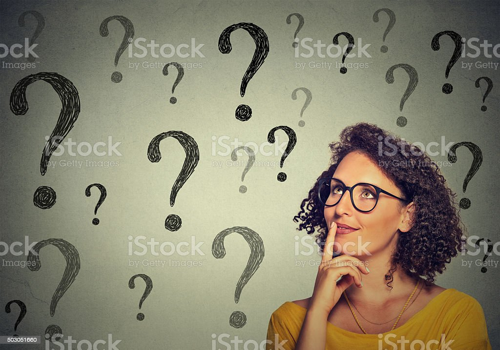 Thinking woman in glasses looking up at many question marks stock photo