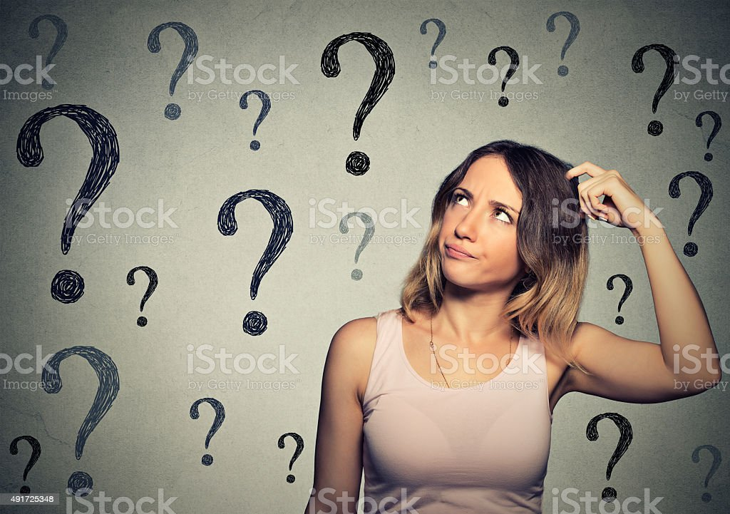 Thinking woman looking up at many question marks stock photo