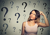 Thinking woman looking up at many question marks