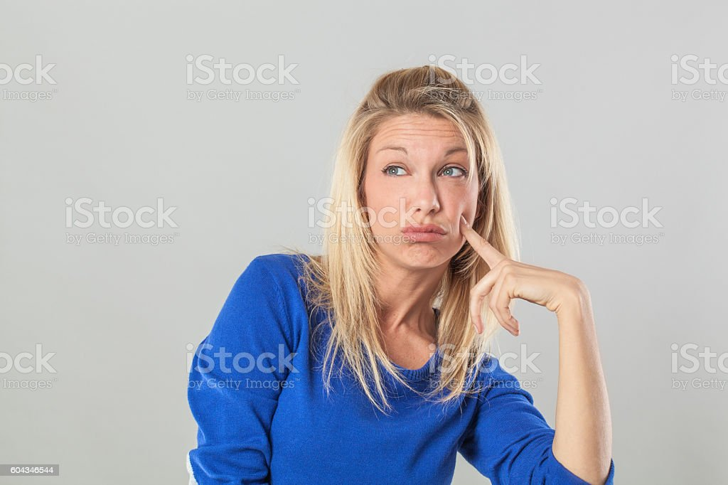 thinking young blond woman looking away with index on cheek stock photo