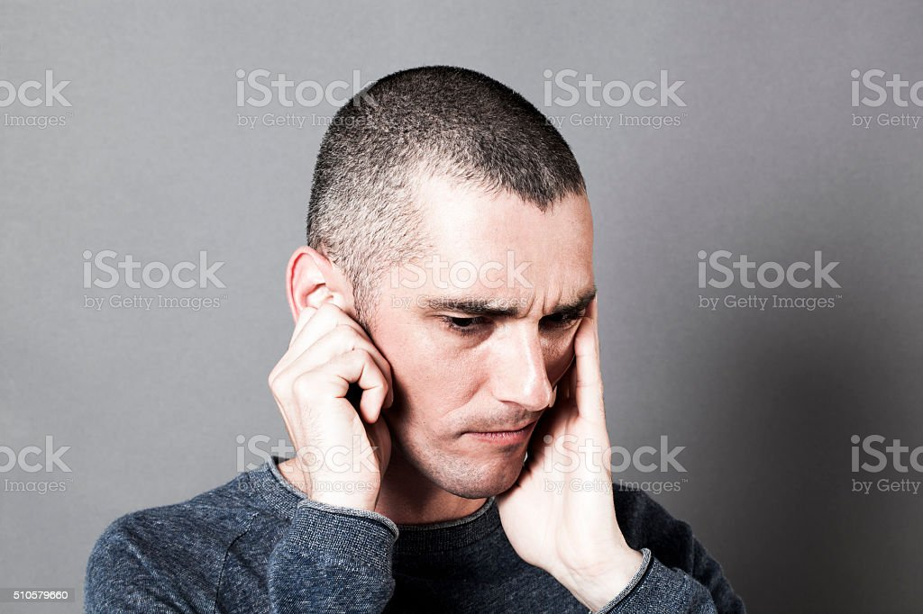 thinking young man suffering from earache covering his ears stock photo