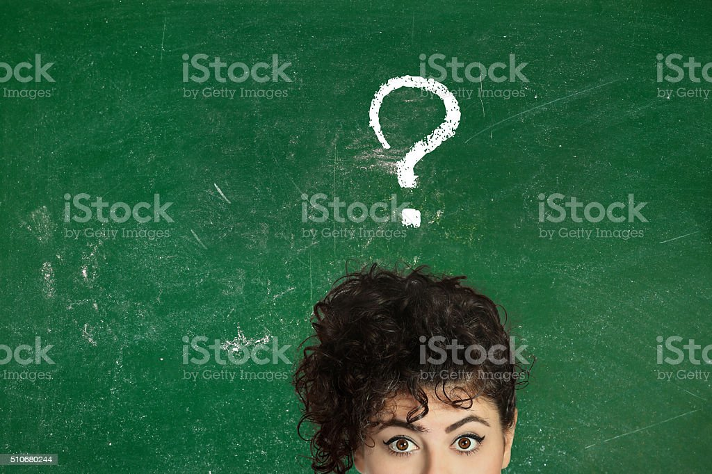 Thinking young woman with question mark on blackboard stock photo