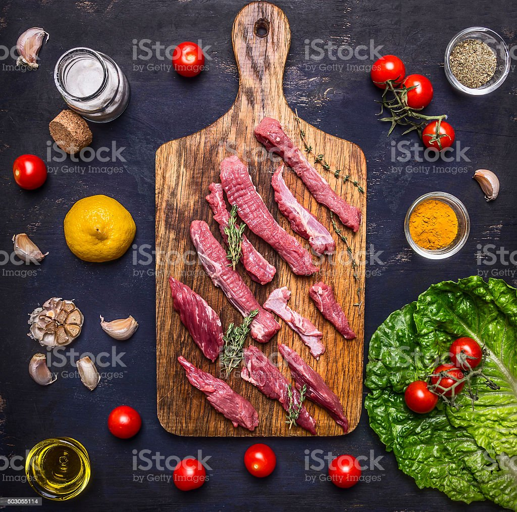 thinly sliced lamb with garlic  cutting board  top view stock photo