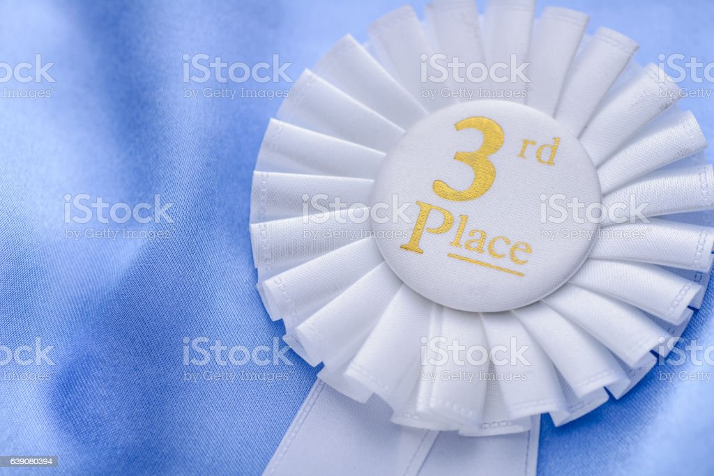 Third place winners white rosette with gold text stock photo