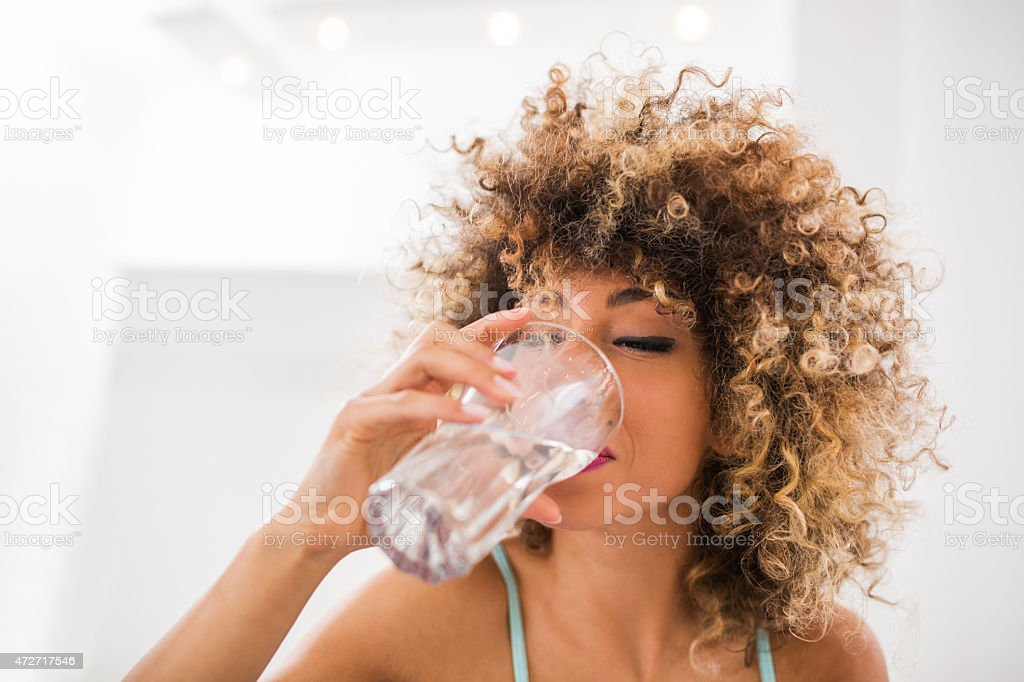 Thirsty African American woman drinking water. stock photo