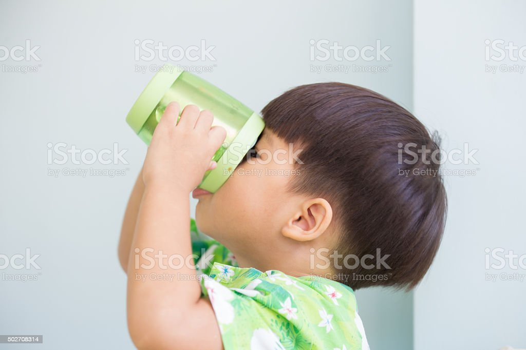 thirsty asian boy drinking by hold up the cup stock photo