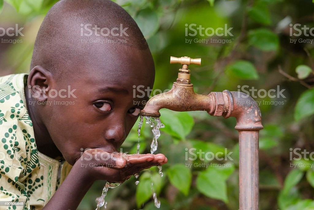 Thirsty Black African Child drinks Clean Fresh Water Tap stock photo
