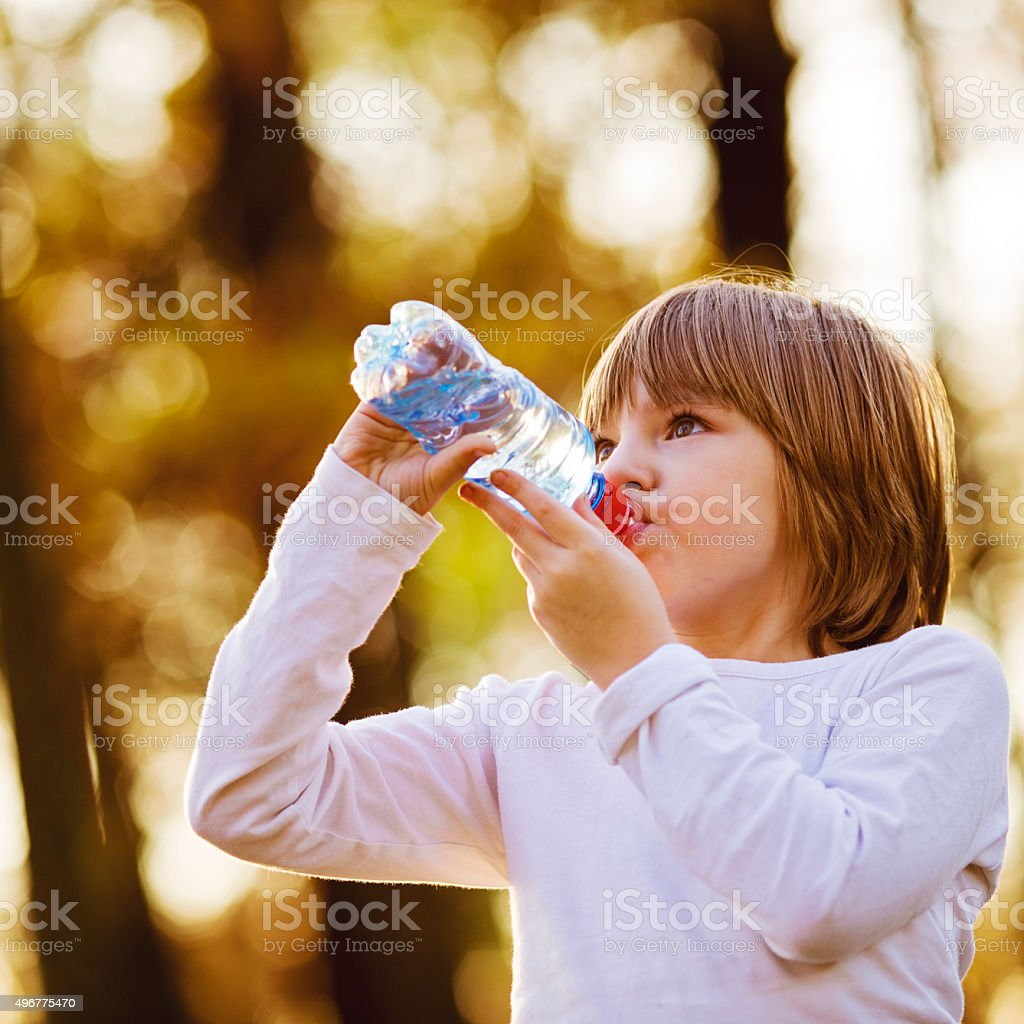 Thirsty Girl Drinking Water Outdoors stock photo