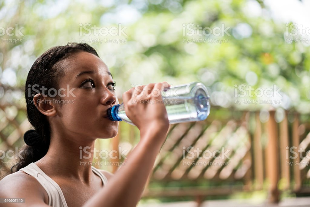 Thirsty Malaysian woman drinking fresh water from the bottle. stock photo