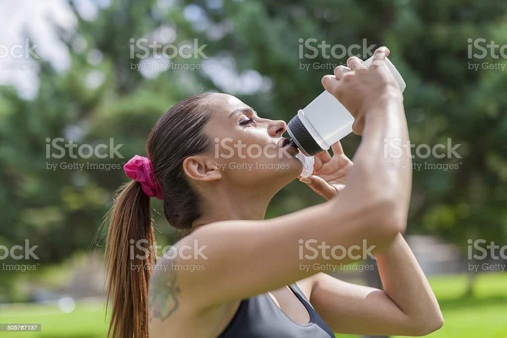 thirsty young woman drinking water while resting stock photo