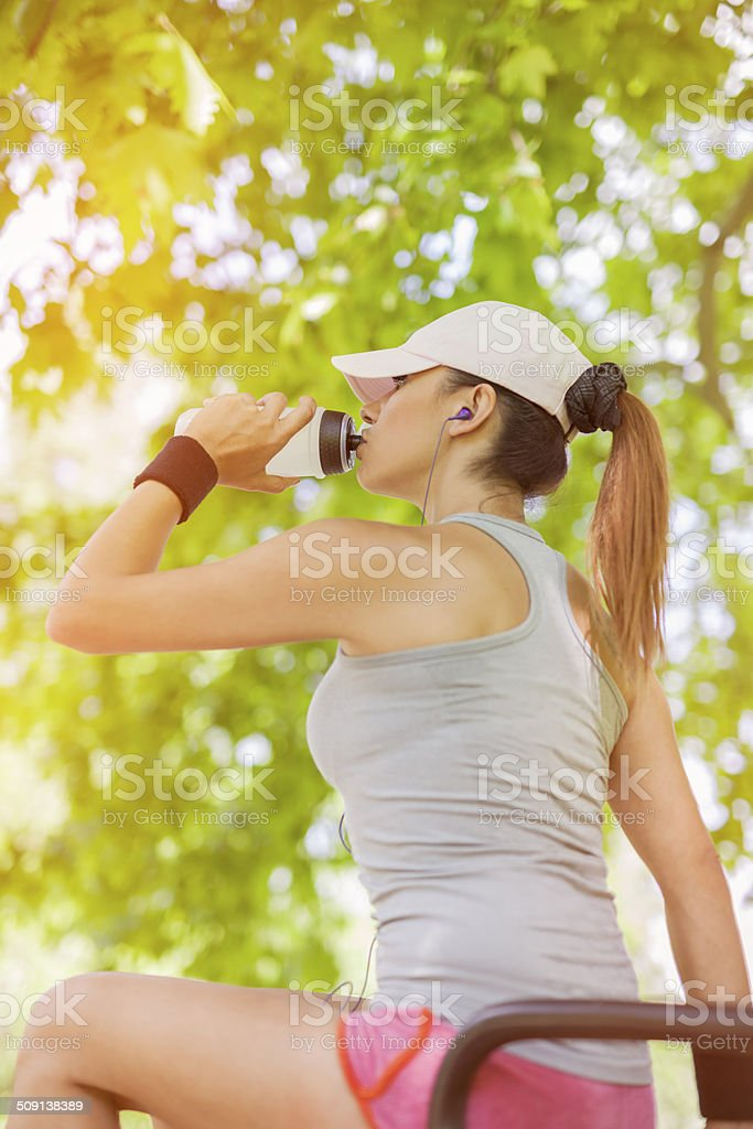 thirsty young woman drinking water while sitting stock photo
