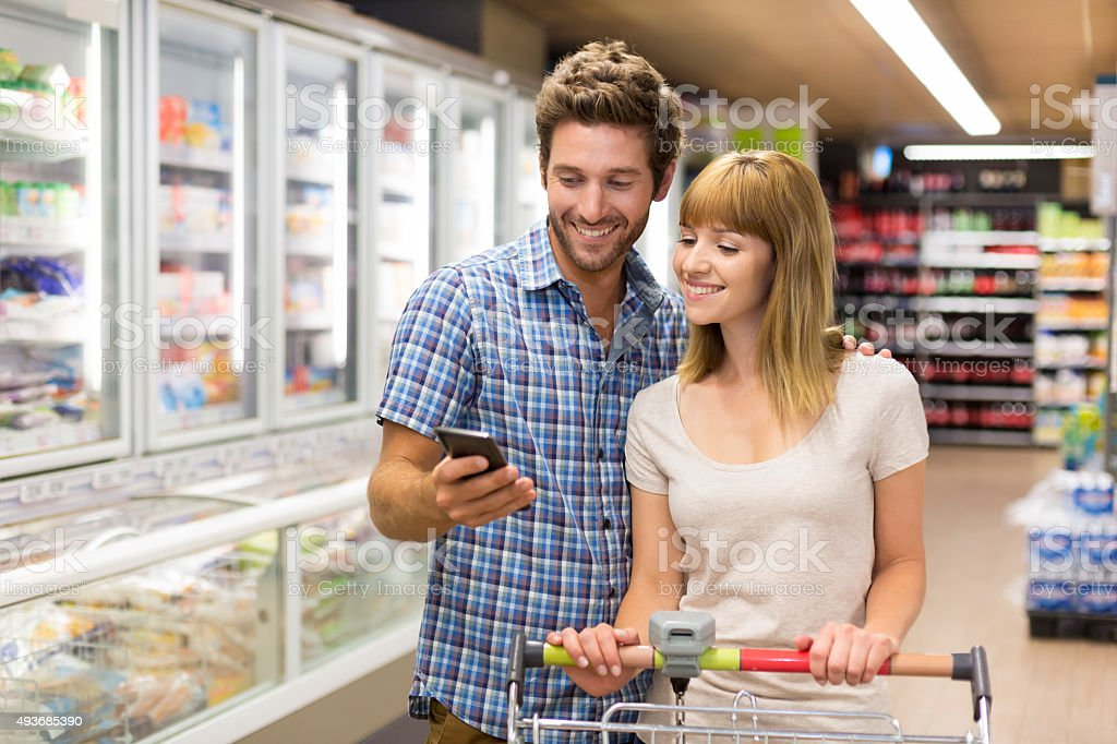 Thirty-year-old couple using mobile phone in supermarket stock photo