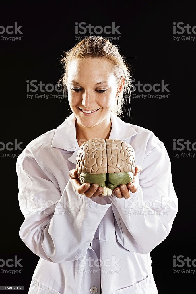 This guy is clueless! Pretty doctor smiles at model brain stock photo