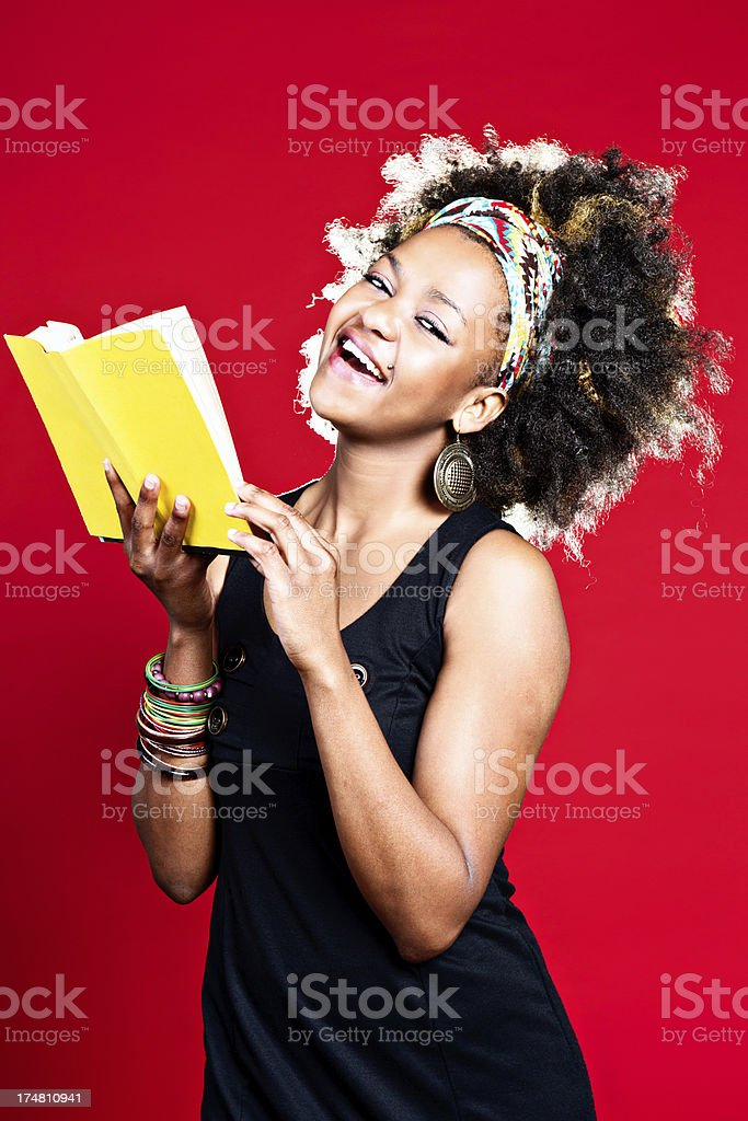 This is hilarious Afro-haired cutie with humorous book royalty-free stock photo