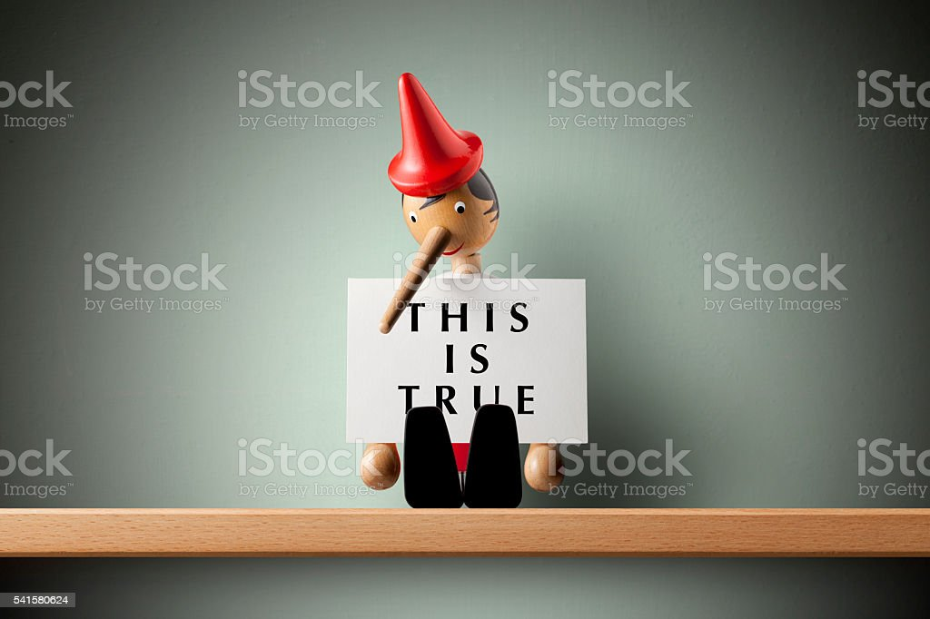 This is true. Pinocchio holding sheet of paper. stock photo