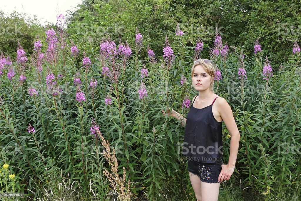 Outdoor girl in wildflower meadow pink fireweed Mitcham Common stock photo
