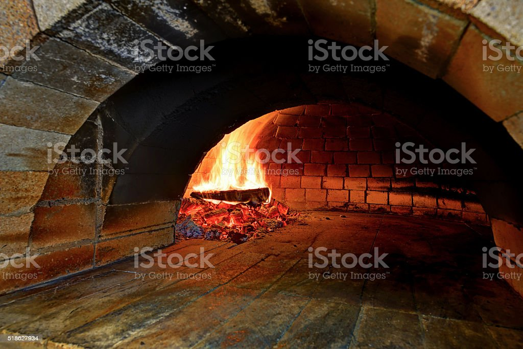 This wood-burning pizza oven on fire. The flame burns inside stock photo