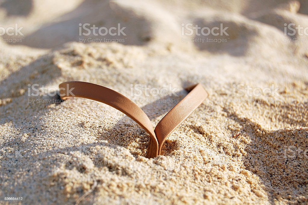 Thong sandal detail in sand stock photo