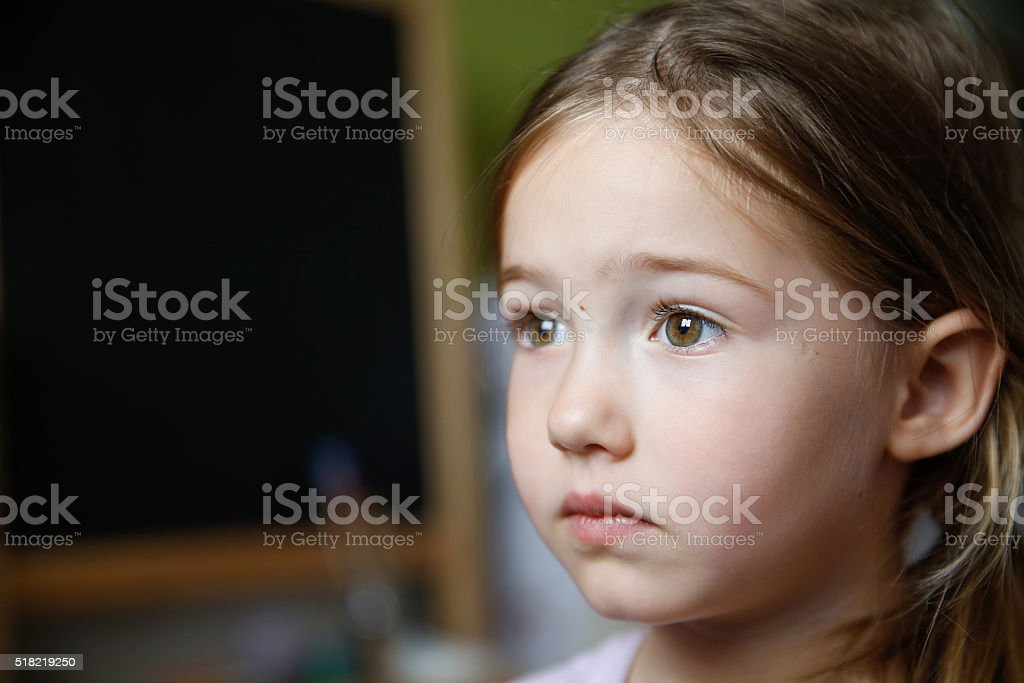 Thoughtful and sad little girl stock photo