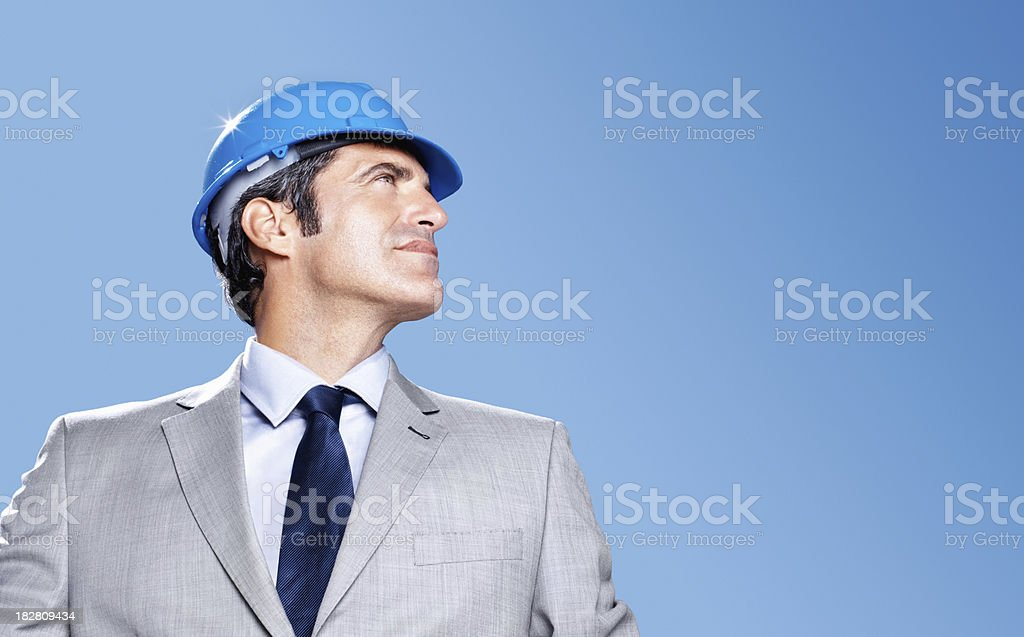 Thoughtful architect looking at copyspace against blue sky royalty-free stock photo