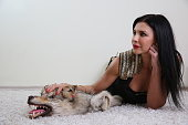 Thoughtful attractive woman lying on carpet with stuffed wolf