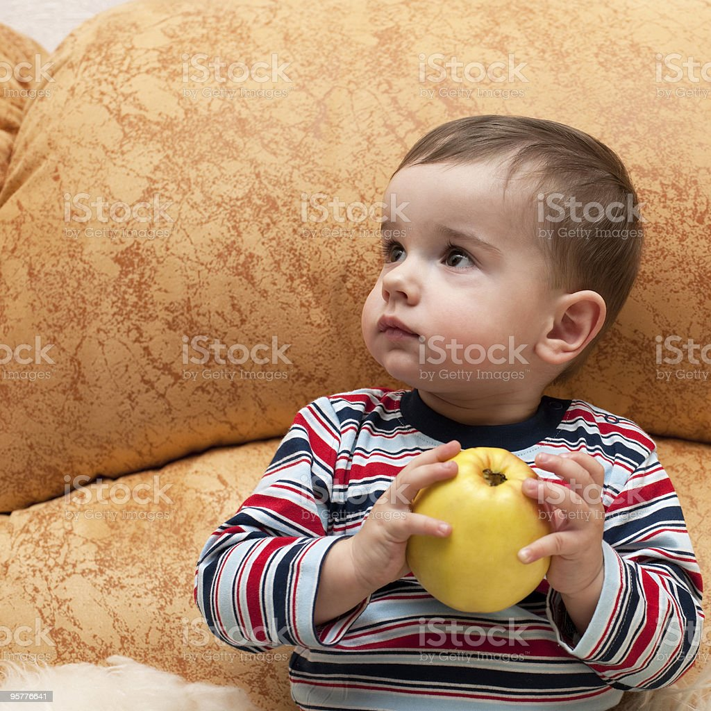 Thoughtful baby with apple royalty-free stock photo