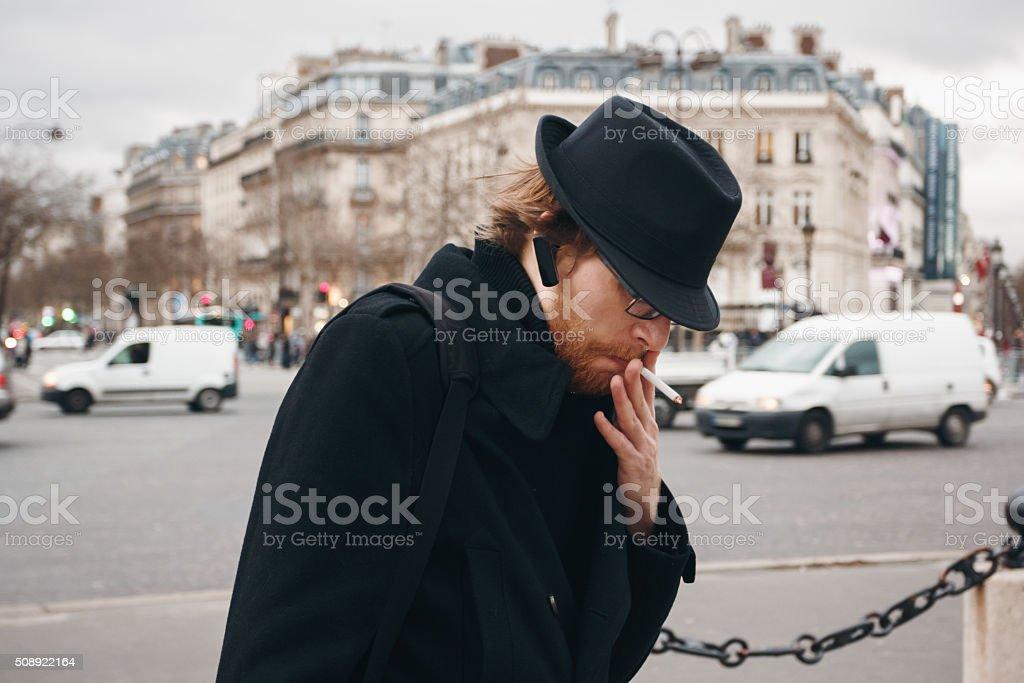 Thoughtful Bearded Man Wearing Hat Smoking stock photo