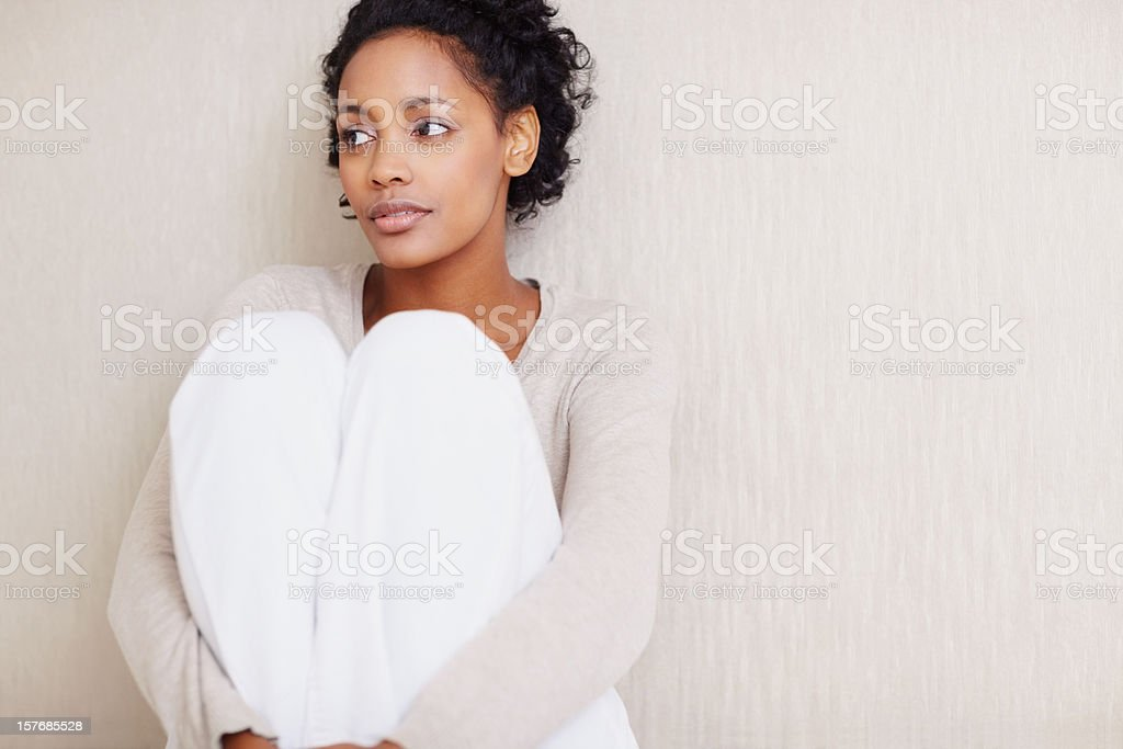 Thoughtful black woman sitting against wall - copy space royalty-free stock photo