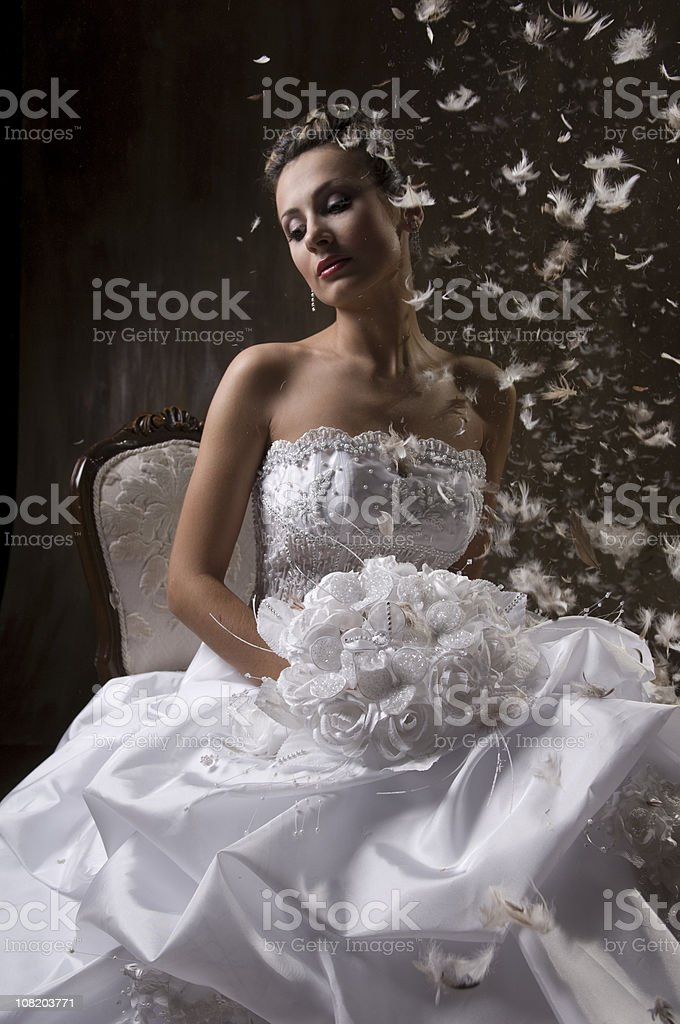 Thoughtful Bride Sitting on Chair with Feathers Floating Around Her royalty-free stock photo
