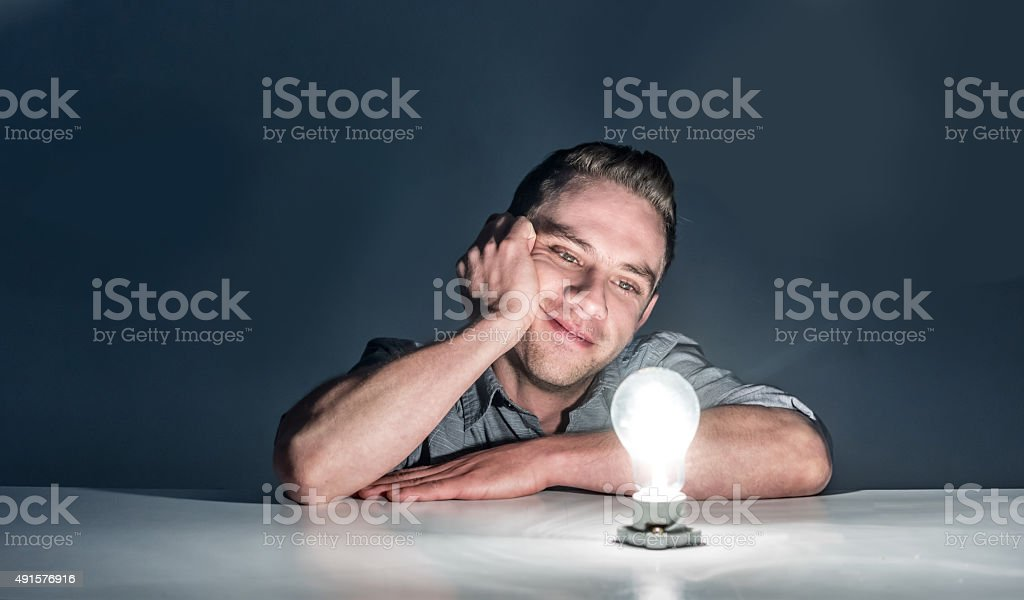 Thoughtful business man looking at a lit light bulb stock photo