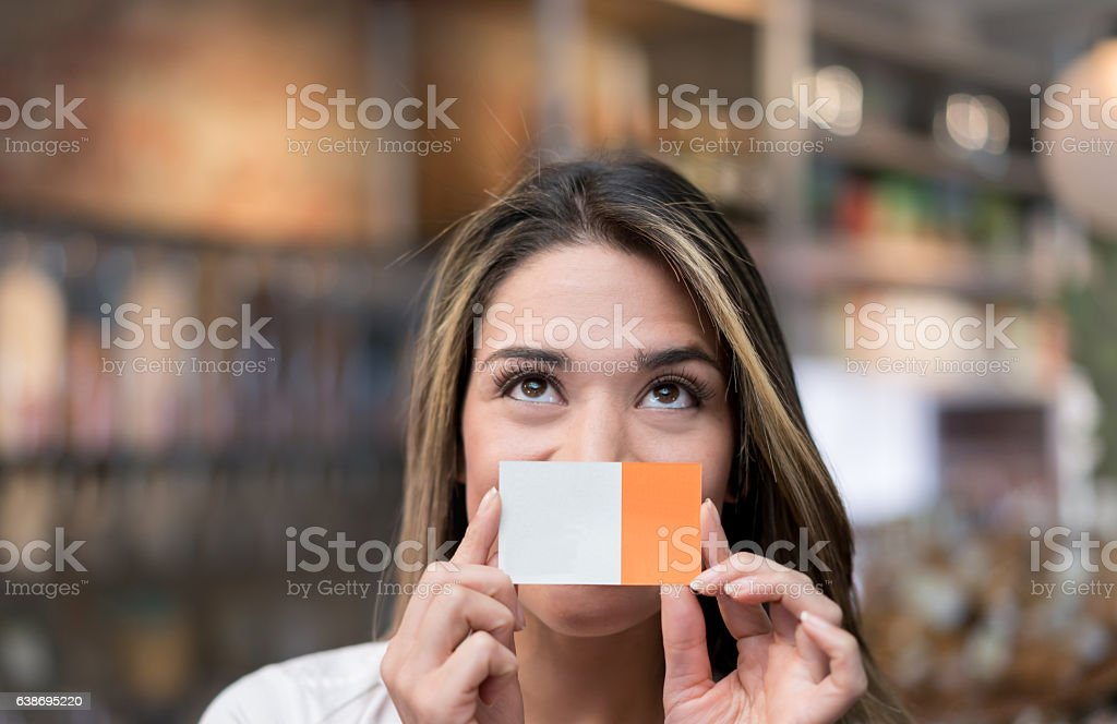 Thoughtful business owner holdign a business card stock photo