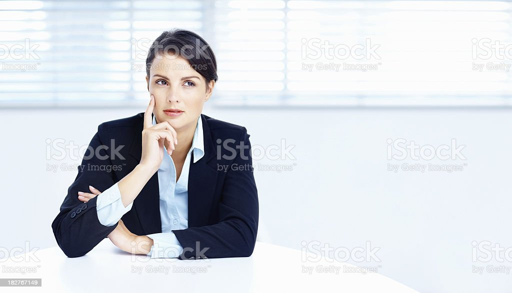Thoughtful business woman sitting at a table royalty-free stock photo