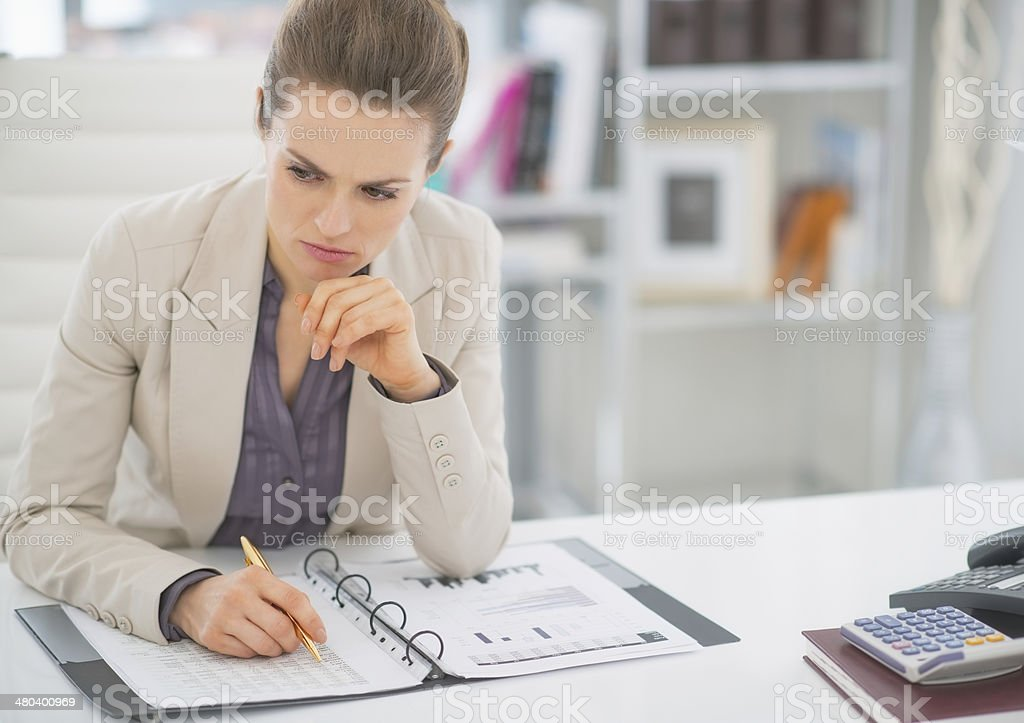 thoughtful business woman working with documents in office stock photo