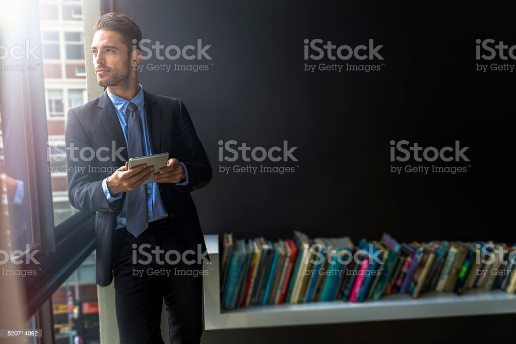 Thoughtful businessman holding digital tablet stock photo