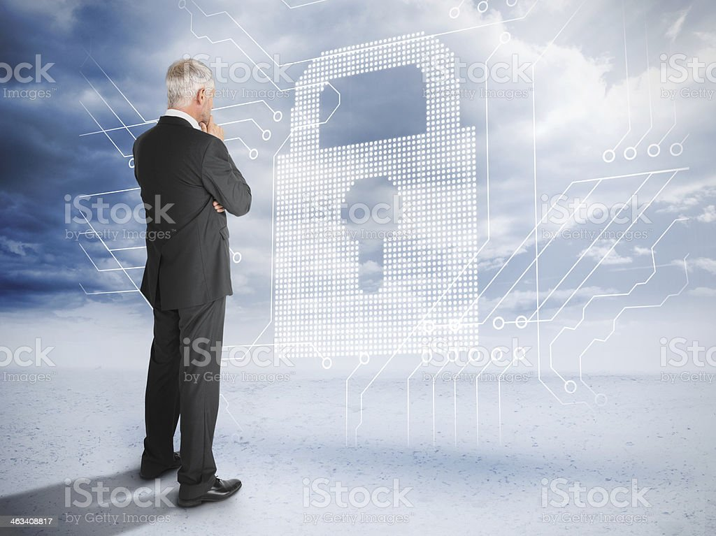 Thoughtful businessman looking at a giant padlock stock photo