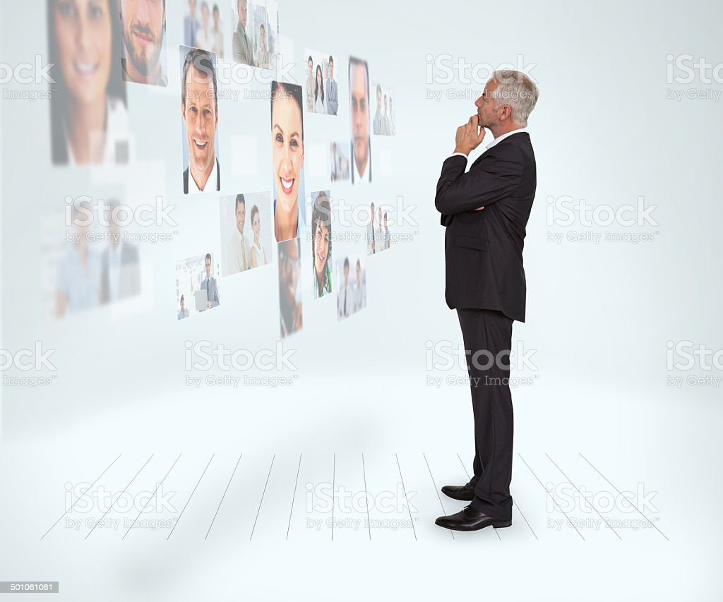 Thoughtful businessman looking at a wall covered by profile pictures stock photo