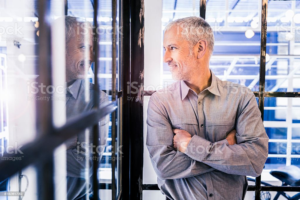 Thoughtful businessman looking out through glass wall stock photo