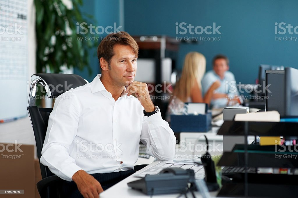 Thoughtful businessman sitting at desk in office stock photo