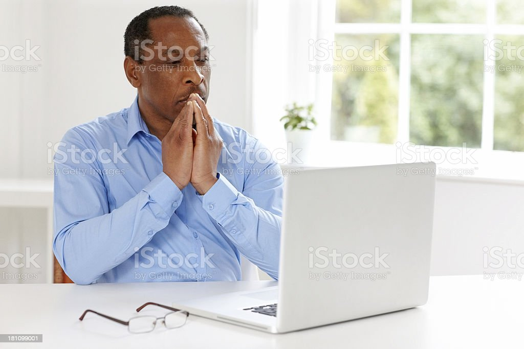 Thoughtful businessman sitting at his desk royalty-free stock photo