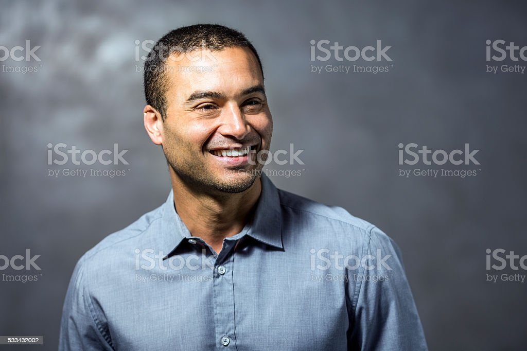 Thoughtful businessman smiling against wall stock photo