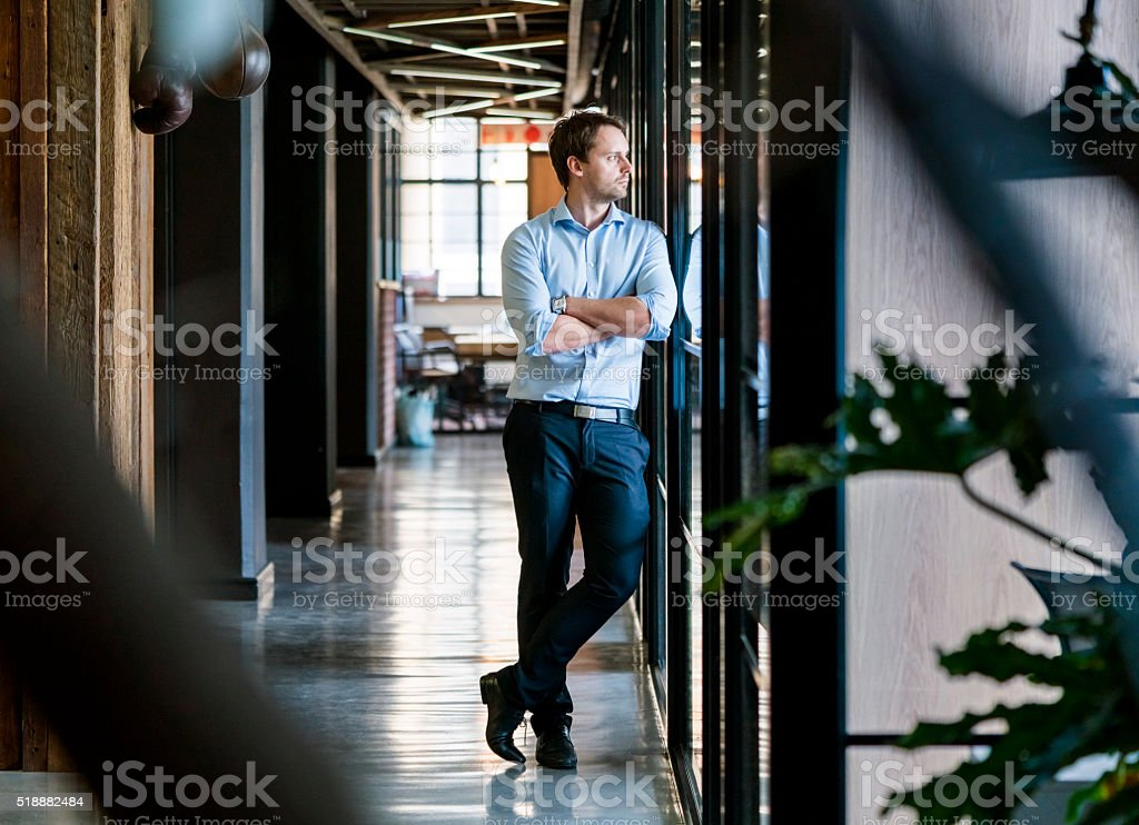 Thoughtful businessman standing arms crossed in office stock photo