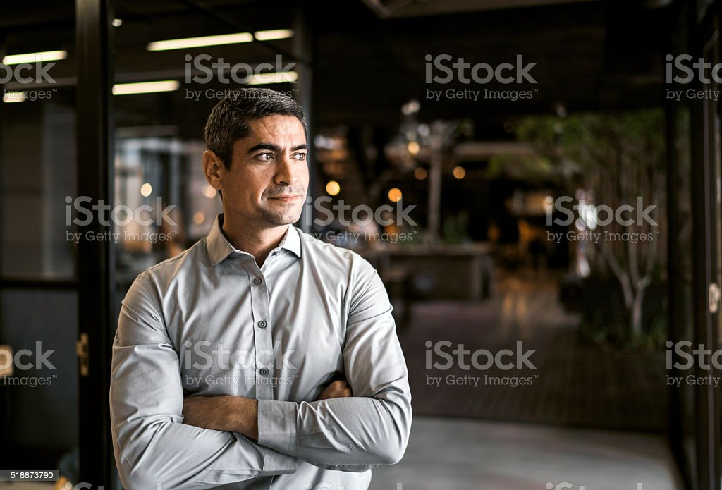 Thoughtful businessman with arms crossed in office stock photo