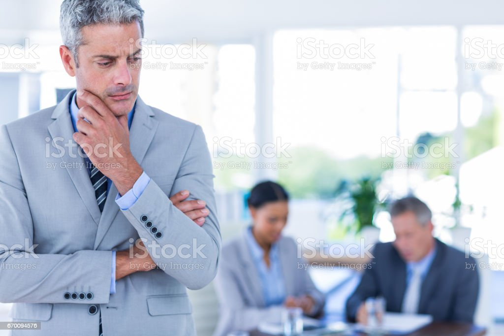 Thoughtful businessman with his colleagues behind him stock photo