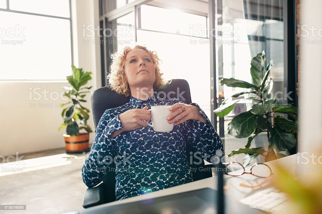 Thoughtful businesswoman at desk in office stock photo