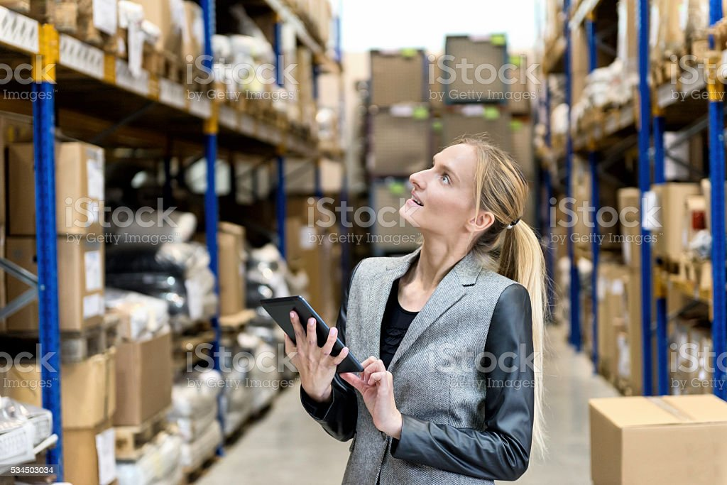 Thoughtful businesswoman in warehouse stock photo