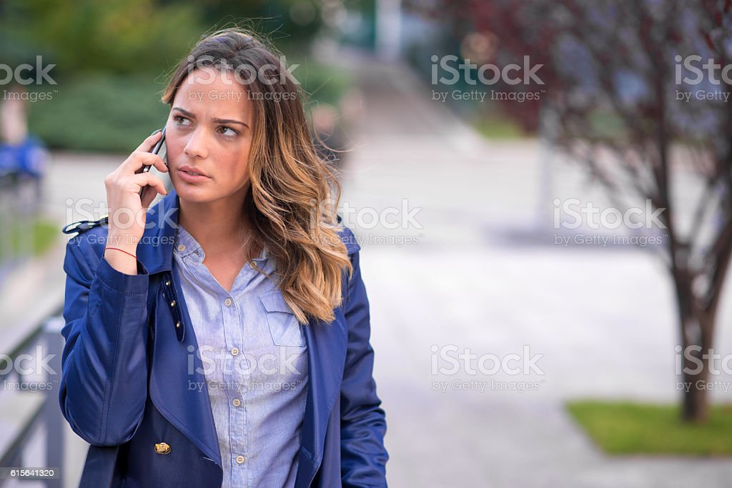 Thoughtful businesswoman talking with her smartphone outside stock photo