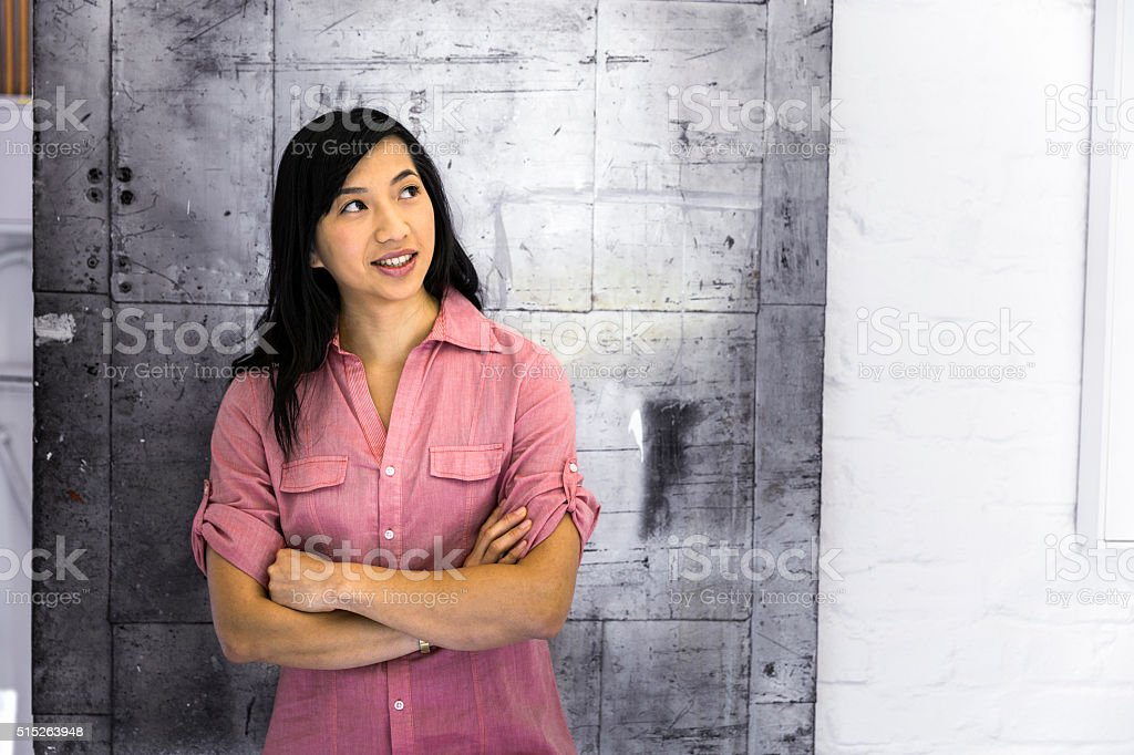 Thoughtful businesswoman with arms crossed in office stock photo