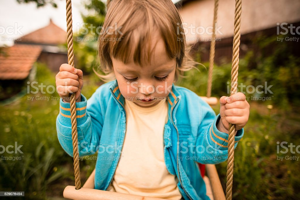Thoughtful child on seesaw stock photo