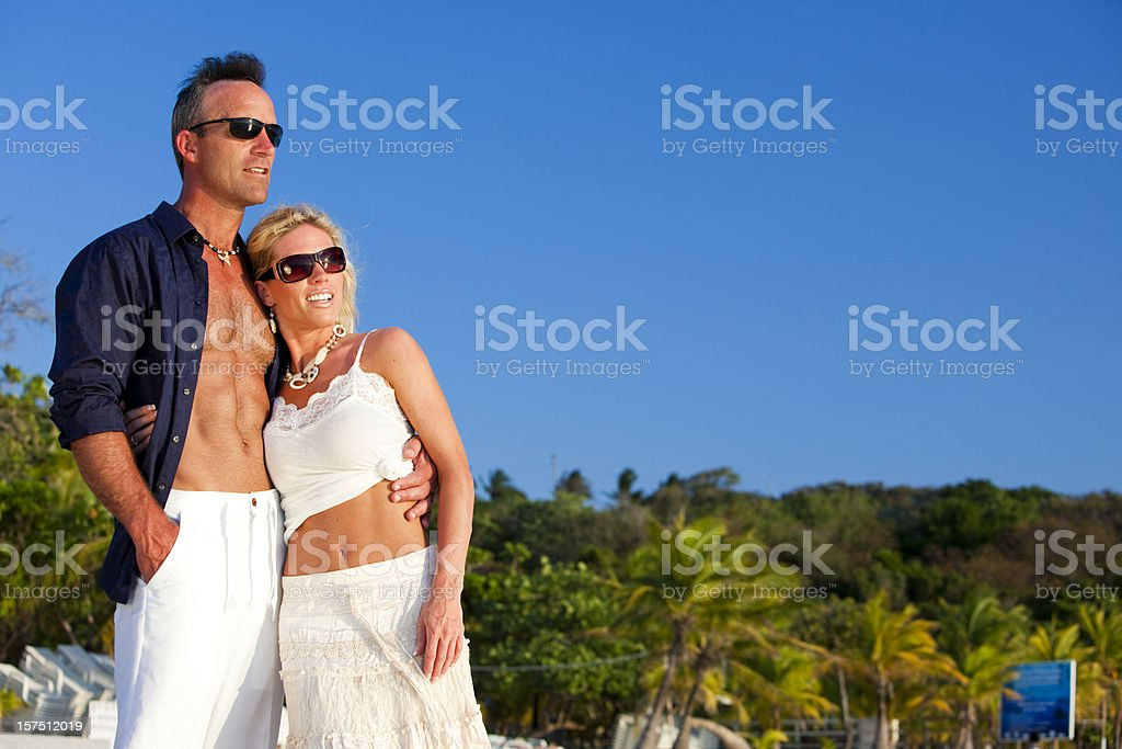 Thoughtful couple on beach looking into distance royalty-free stock photo