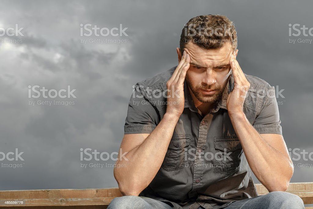 Thoughtful, depressed, handsome man in a park stock photo